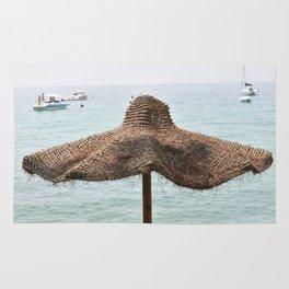 Beach umbrella in natural fibers on the shore of Lake Garda Rug