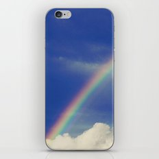 Rainbow over fluffy white clouds in the blue sky iPhone & iPod Skin