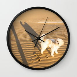 Shadows of a dog and his master on the sand in winter just after dawn Wall Clock