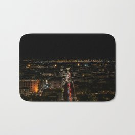 Night view of the illuminated city, the trails of car lights cut the scene in two Bath Mat