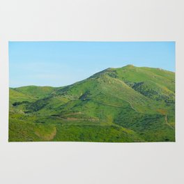 green field and green mountain with blue sky Rug