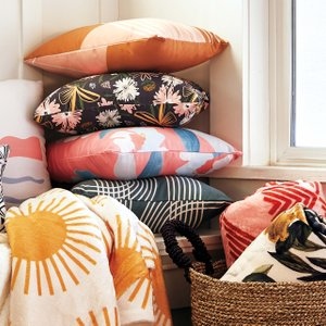 pillows and blankets stacked in a sunlit corner