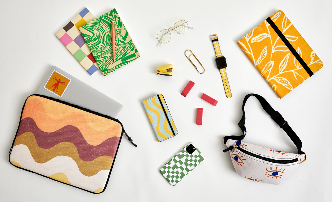 flatlay with retro laptop sleeve, checkered iphone case, fanny pack and more
