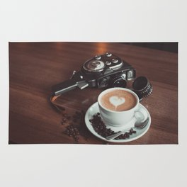 A cup of hot cappuccino placed on a table next to the old camera with lens and coffee beans Rug
