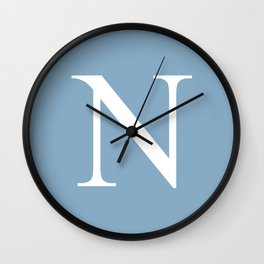 Letter N sign on placid blue background Wall Clock