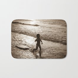 Little surfer girl runs in the waves with her bodyboard Bath Mat