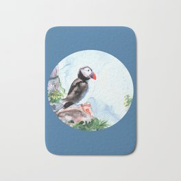 Puffin sitting on a rock with a blue background Bath Mat