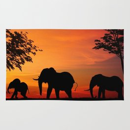 Elephants in the African sunset Rug