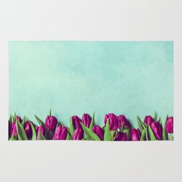Purple tulips border, fresh spring flowers on rustic blue background with copy space Rug