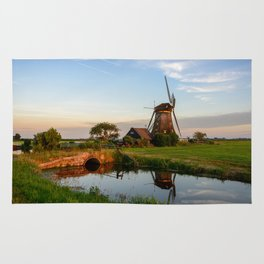 Windmill in a countryside landscape in Holland at sunset Rug