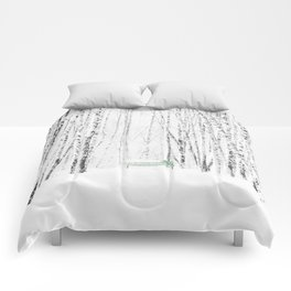 Green bench in white winter forest Comforters