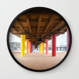 Pier with color painted columns on the beach Wall Clock