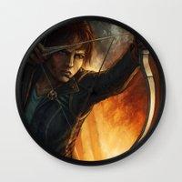 katniss Wall Clocks featuring Katniss Everdeen by Emily Doyle