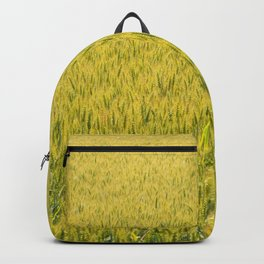 Expanse of wheat in a field under the spring sun Backpack