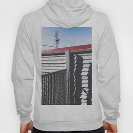 steel fence and wooden fence with red building in the city Hoody