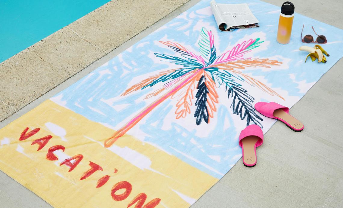 palm tree beach towel next to a pool