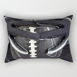 Black gloved hands holding a black American Football Rectangular Pillow