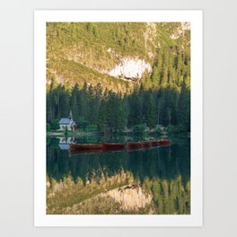 Row of wooden boats in front of a church reflected in the water Art Print