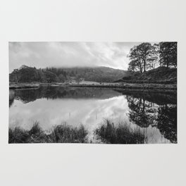 Dramatic sky and reflections on the River Brathay at Elter Water. Lake District UK. Rug