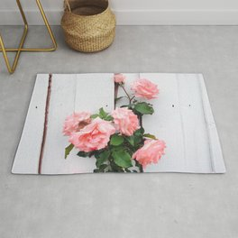 pink rose garden with white wood wall background Rug