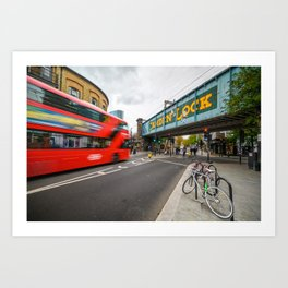 Long exposure of the painted Camden Lock bridge across Camden High Street with a blurred red London Double Decker bus approaching Art Print