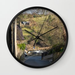 A view along a road down a hill towards a the River Swale and fields in Richmond, North Yorkshire Wall Clock
