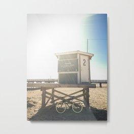 Bike leaning against lifeguard hut on beach Metal Print