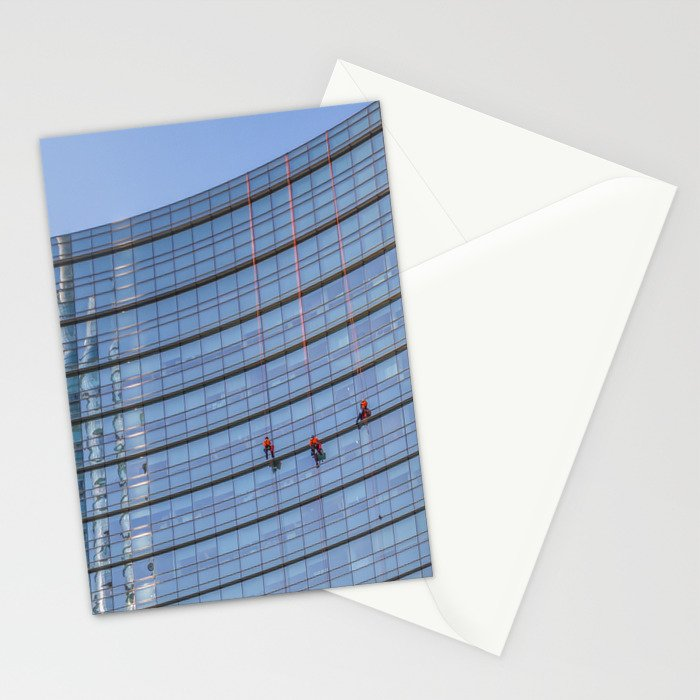 three workers work to clean the windows of a large skyscraper in Milan Stationery Cards