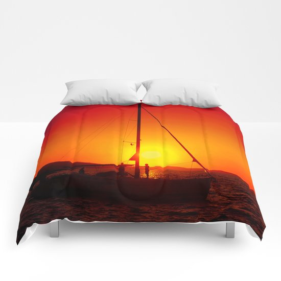 A sailboat at sunset Comforters