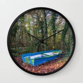 Old blue and green boat abandoned aground in a forest in a natural park Wall Clock