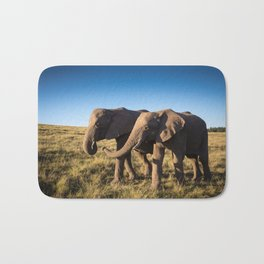 Two happy elephants walking together in African Savannah at sunset Bath Mat