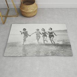 Four women run in water on the beach Rug