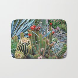 Closeup of a flowering cactus and other plants in a garden Bath Mat