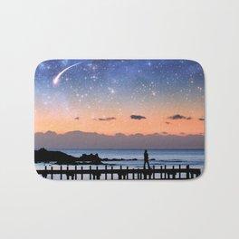 Fantasy landscape - silhouette of a woman walking on pier admiring stars in the sky.  Bath Mat