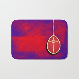Gold cross in red egg hanging against a rich red and purple Bath Mat