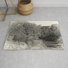 Black and white study of a tranquil river Rug