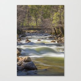 A bridge over the Merced River stands solidly over the velvety exposure of the water Canvas Print