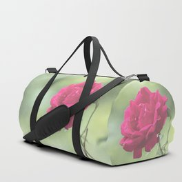 Wild red rose on green blurry background Duffle Bag
