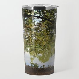 A bench under a tree Travel Mug