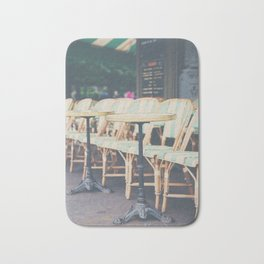 tables & chairs outside of a Paris cafe Bath Mat