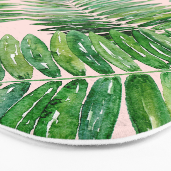 Green palm leaves on a light pink background. Bath Mat