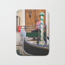Gondolier wearing traditional striped shirt having a rest at the pier Bath Mat