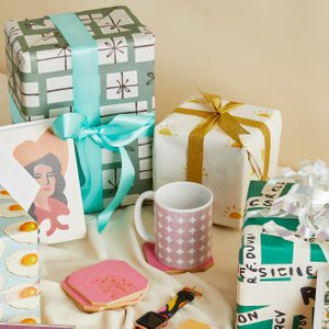 flatlay with wrapped presents, checkered water bottle, cards, mugs and more gifts