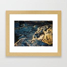 The sun is setting over the rocks Framed Art Print
