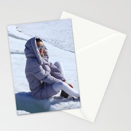 Girl in warm down-padded coat enjoys a look at snow top. Stationery Cards