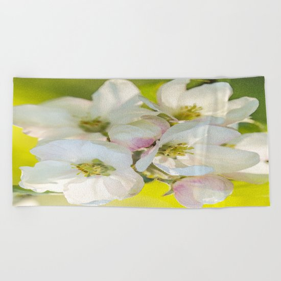 Close-up of Apple tree flowers on a vivid green background - Summer atmosphere Beach Towel
