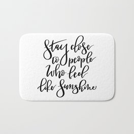 Stay close to people who feel like sunshine black lettering Bath Mat