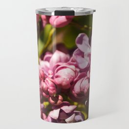 Branch of fresh purple lilac flowers in a city public park close-up Travel Mug