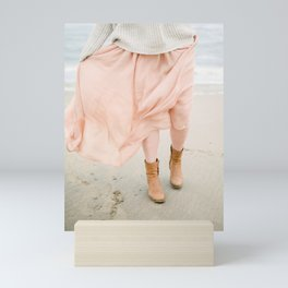 Coastal photography of a woman holding her flowy skirt at the beach. Pastel colored print Mini Art Print