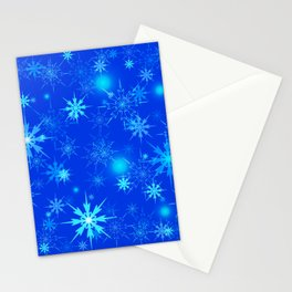 Pattern of luminous light blue snowflakes on a light background with bright highlights. Stationery Cards